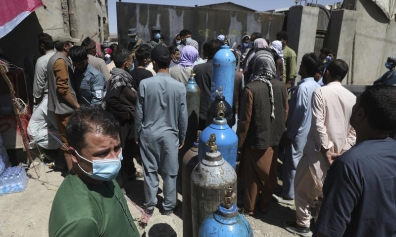 Men wait outside a privately owned oxygen factory to get their oxygen cylinders refilled, in Kabul, Afghanistan, June 19. — AP