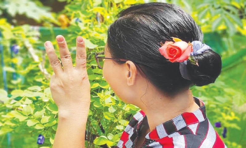 A woman making the three-finger salute as she wears flowers in her hair as part of a social media campaign to mark the birthday of Myanmar's detained civilian leader Aung San Suu Kyi in Yangon.— AFP