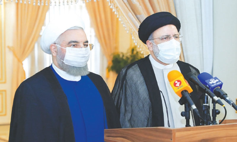 Iran's outgoing President Hassan Rouhani and Iran's President-elect Ebrahim Raisi speak to the media after their meeting in Tehran on Saturday.—Reuters