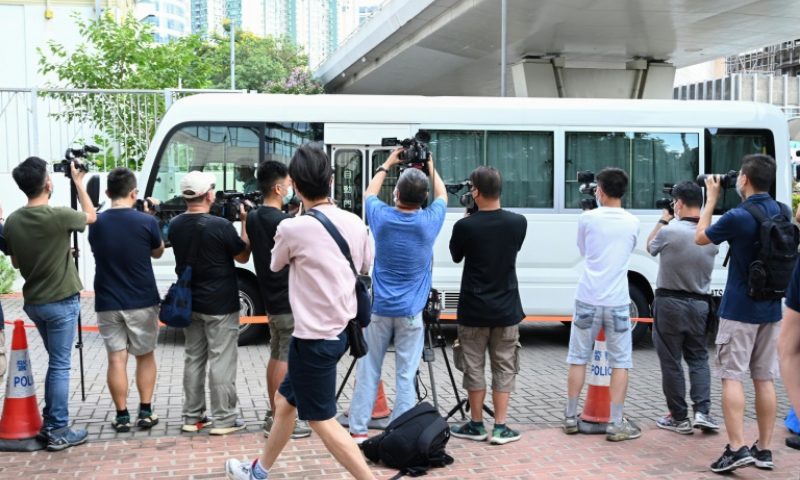 A van believed to be carrying the two executives arrives at court. — AFP