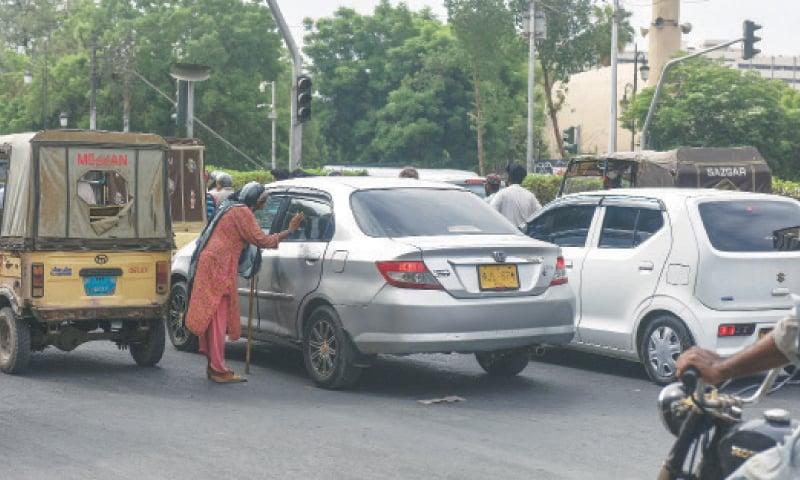 A BEGGAR seeks alms from a motorist at a traffic signal.—White Star