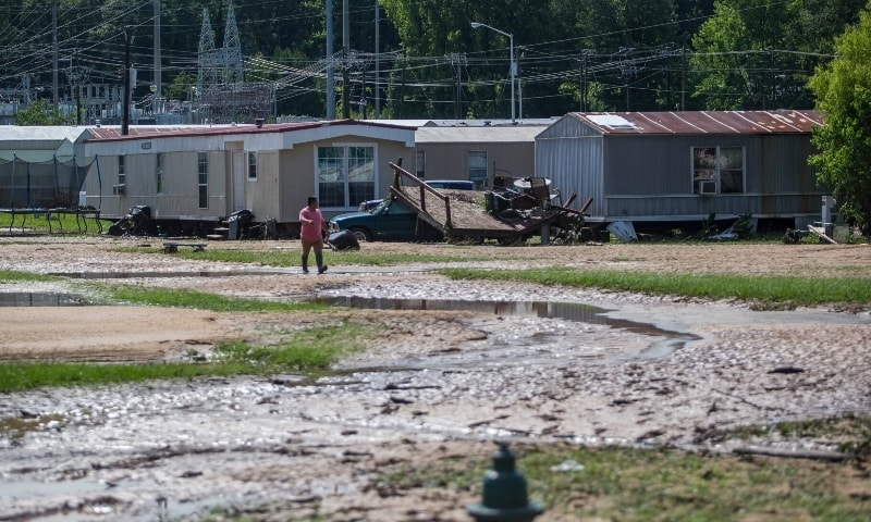 A resident walks through a partially flooded trailer park in Northport, Alabama on June 20. — AP
