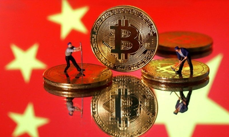 Small toy figurines are seen on representations of the Bitcoin virtual currency displayed in front of an image of China's flag in this illustration picture. — Reuters/File