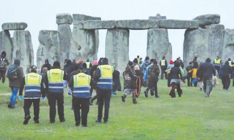 Security officials look on as people run to Stonehenge ancient stone circle during the summer solstice celebrations.—Reuters