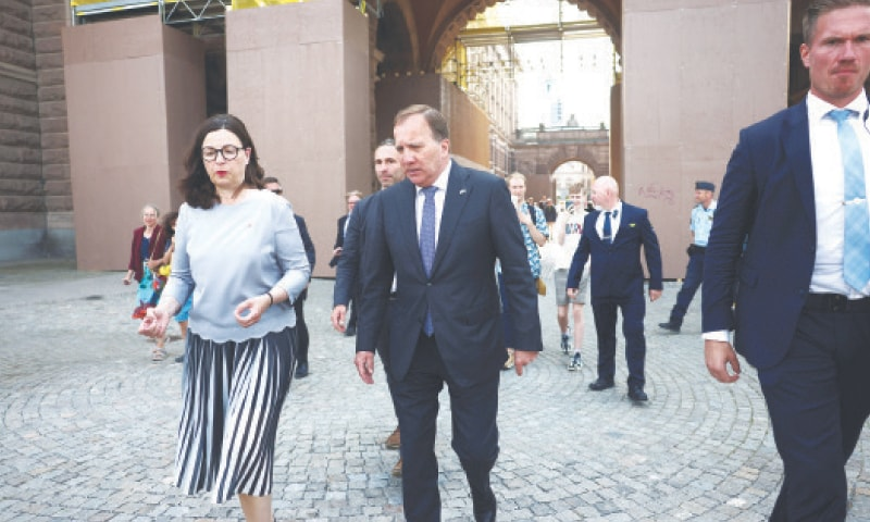 Sweden's Prime Minister Stefan Lofven and Education Minister Anna Ekstrom walk away after the no-confidence vote.—Reuters