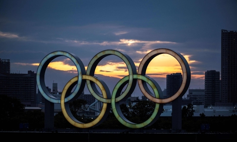 This file photo taken on April 28 shows a general view shows the Olympic rings lit up at dusk on the Odaiba waterfront in Tokyo. — AFP