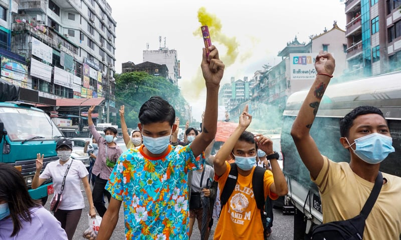 A protester holds a flare as others make the three-finger salute during a demonstration against the military coup in Yangon. — AFP