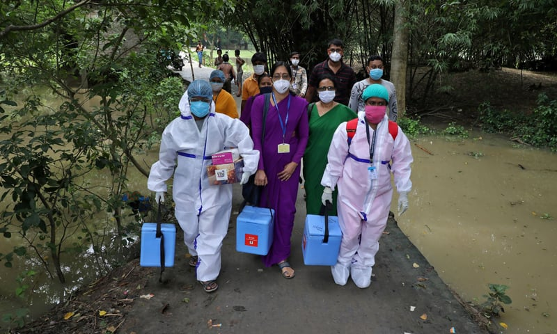 Healthcare workers carry Covishield vaccine, manufactured by the Serum Institute of India, to inoculate villagers during a door-to-door vaccination and testing drive on Uttar Batora Island in Howrah district, India. — Reuters