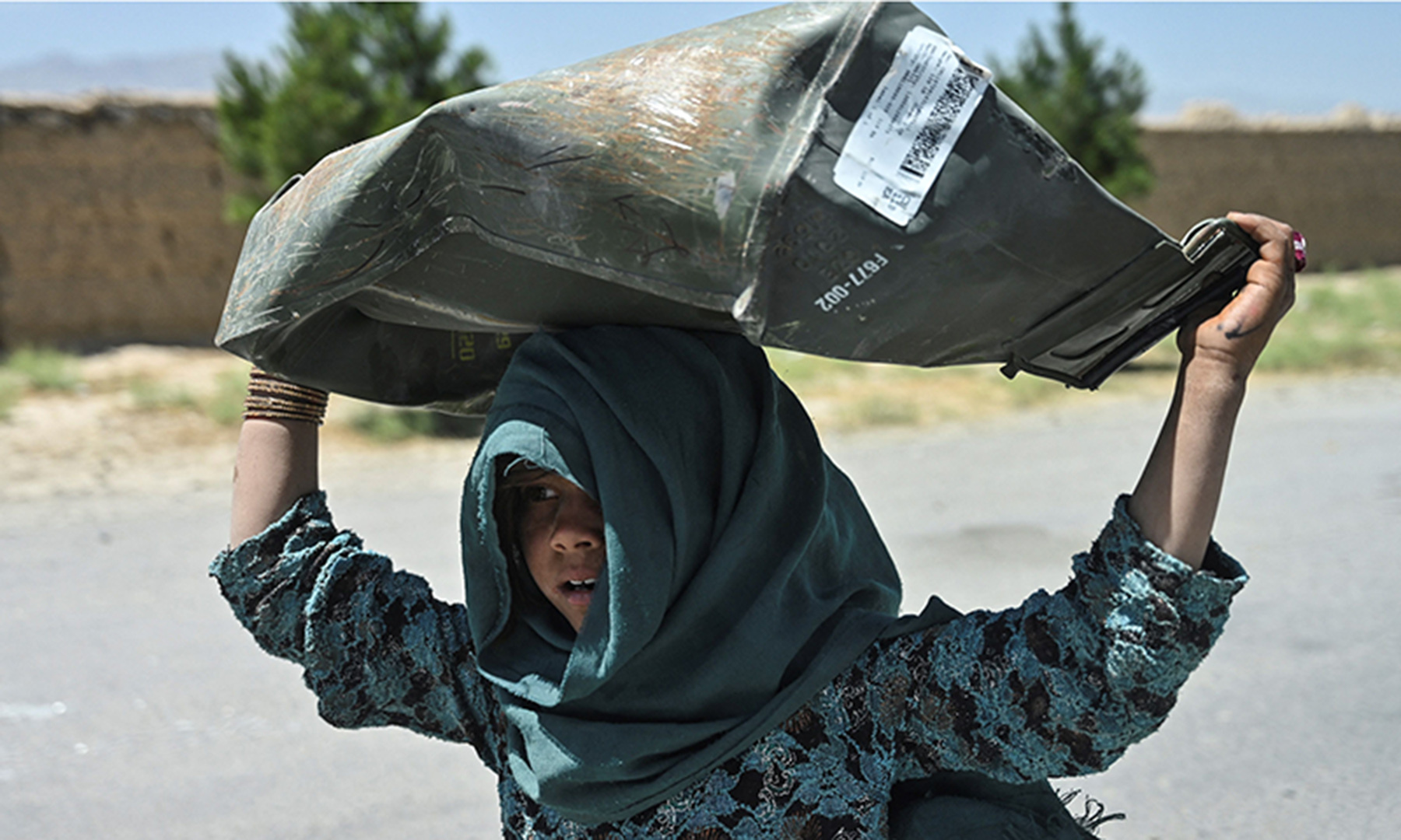 A girl carries a metal box she collected from a junkyard near the Bagram Airbase in Bagram. — AFP