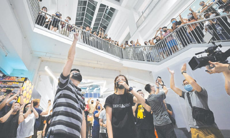 Executive editor-in-chief Lam Man-Chung punches the air as other journalists clap in the Apple Daily's office after preparing an edition for the last time on Wednesday.—AFP