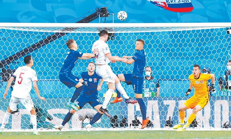 SEVILLE: Spain's Aymeric Laporte (top) heads to score during the Group 'E' match against Slovakia at the La Cartuja Stadium on Wednesday.—Reuters