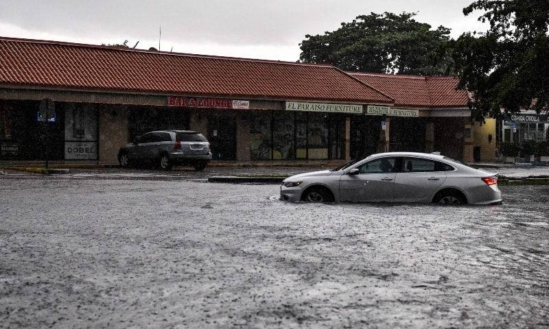 In this file photo taken on May 26, 2020 a woman drives through floodwater during heavy rainfall in Miami. — AFP