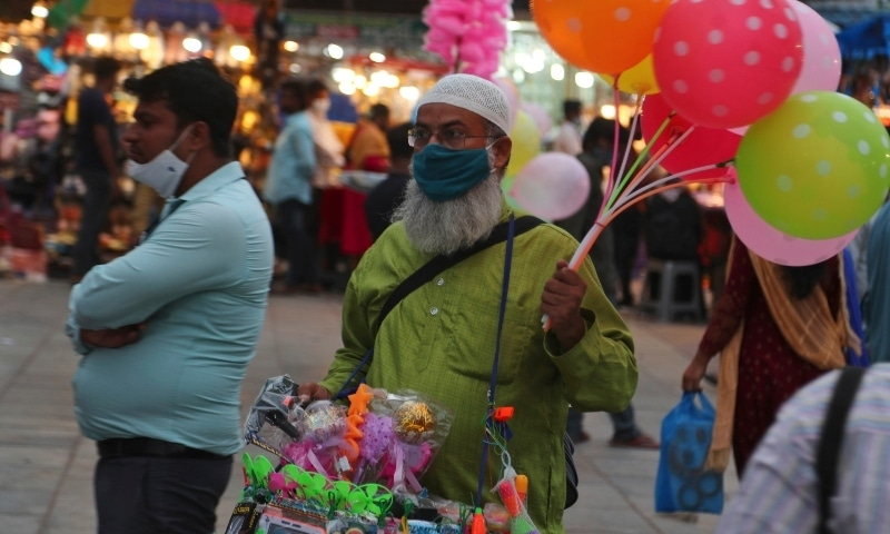 A man wearing a face mask as a precaution against the coronavirus stands on a street selling balloons in Hyderabad, India on June 23. — AP