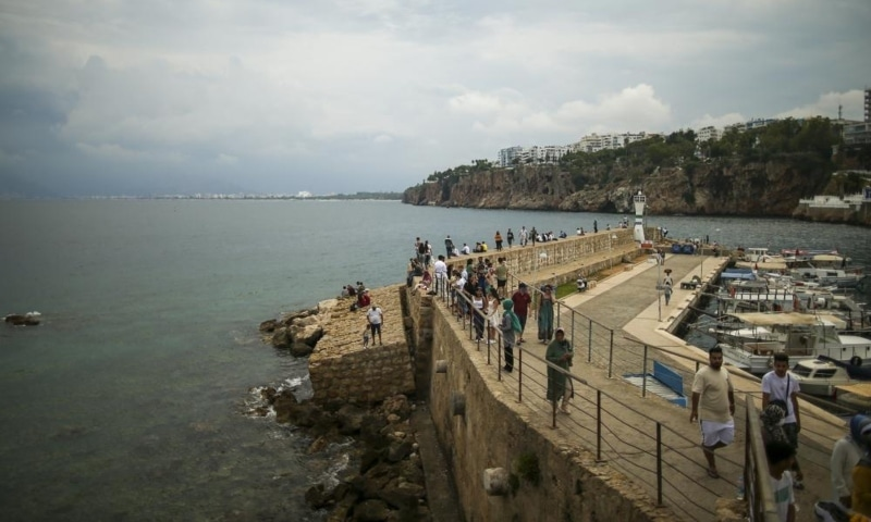 Tourists visit the old harbour, in Antalya, southern Turkey, June 21. — AP