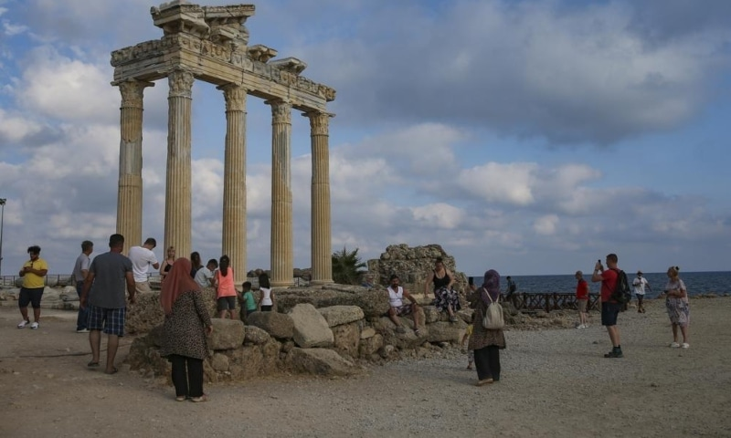Tourists visit the 150AD Roman temple dedicated to Apollo the Greek and Roman god of music, harmony and light, in Antalya, southern Turkey, June 20. — AP