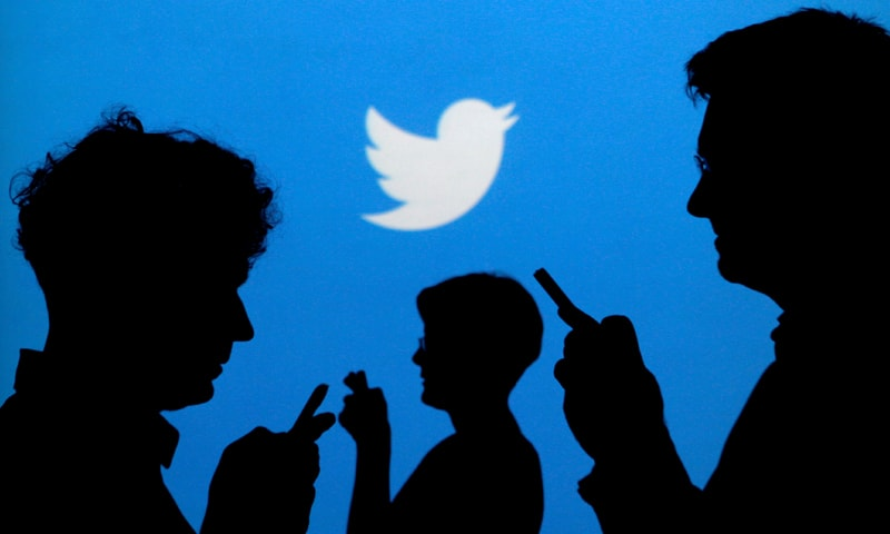 People holding mobile phones are silhouetted against a backdrop projected with the Twitter logo in this illustration picture. — Reuters/File