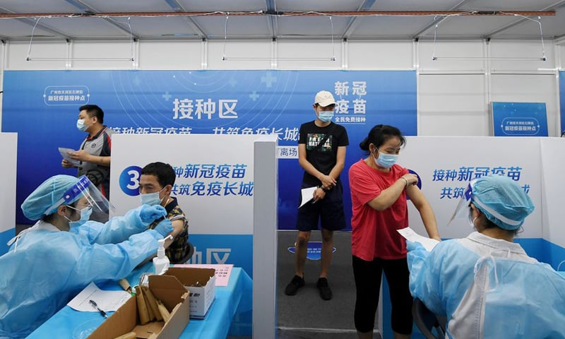 Residents receive vaccines against Covid-19 at a makeshift vaccination site in Guangzhou, China. — Reuters