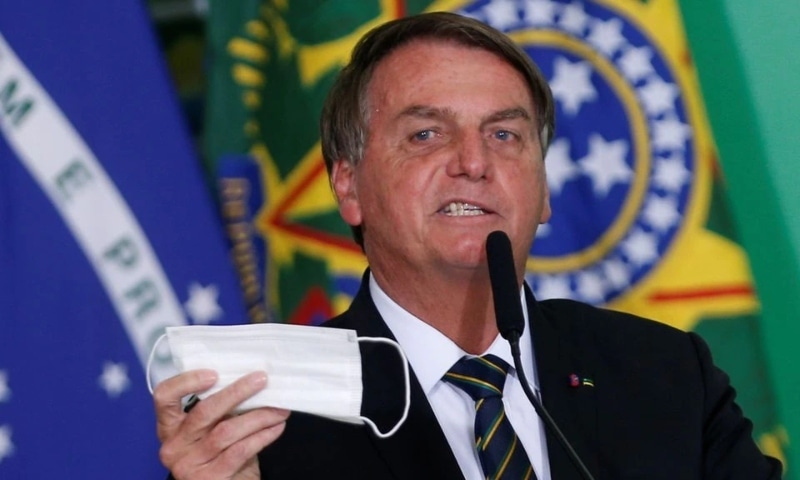 Brazil's President Jair Bolsonaro holds his protective face mask during a ceremony at the Planalto Palace in Brasilia, June 10. —Reuters