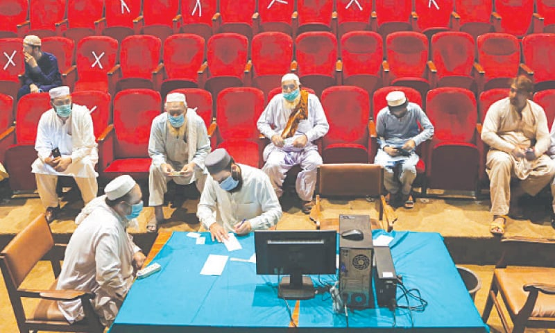PESHAWAR: Citizens completing formalities to get themselves vaccinated against the Covid-19 at Nishtar Hall on Friday. — PPI