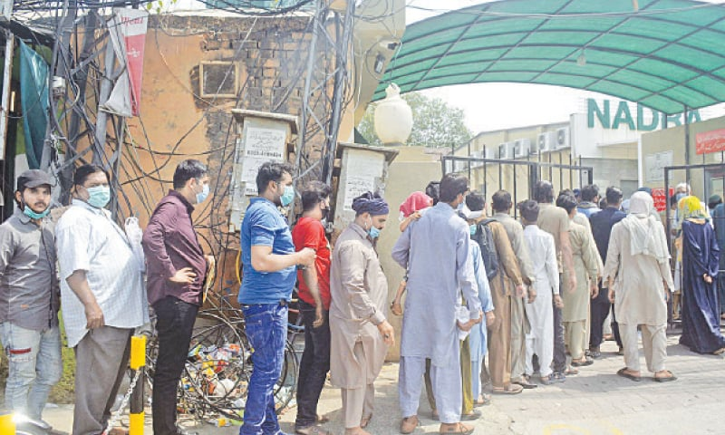 LAHORE: People stand in a queue outside a Nadra office on Friday without maintaining social distancing. — Online