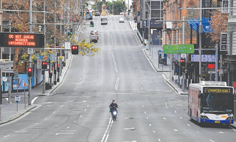 A food delivery worker rides in the central business district of Sydney on Saturday as Australia's largest city entered a two-week lockdown to contain an outbreak of the highly contagious Delta variant. — AFP