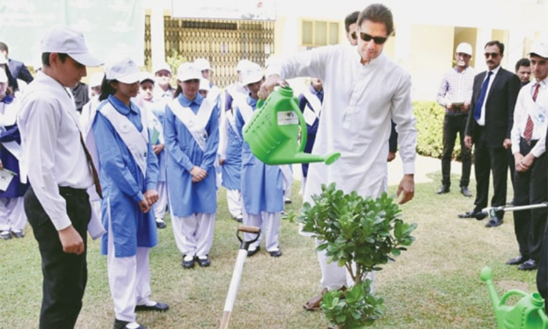 Prime Minister Imran Khan waters a plant during the launch of 'Clean and Green Pakistan' campaign at Islamabad Model College for Girls in Islamabad. — Online/File