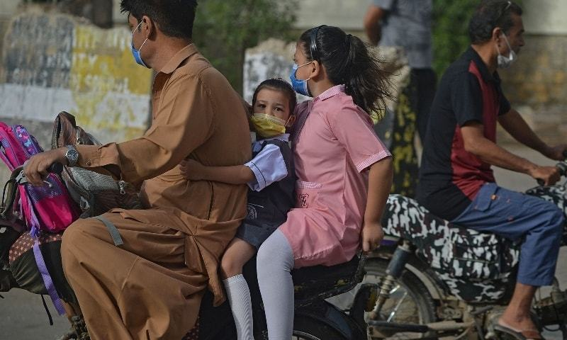 Children riding as a pillion on a motorcycle on their way to a school in Karachi on June 21. — AFP/File