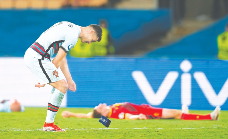 SEVILLE: Portugal's Cristiano Ronaldo throws away the captain's arm-band after the round-of-16 match against Belgium at La Cartuja Stadium.—Reuters