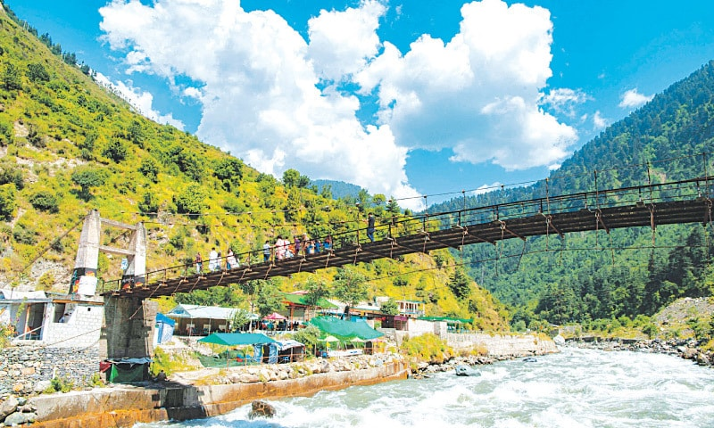VISITORS cross a bridge in Naran valley on Monday after the provincial government lifted the ban on tourists imposed due to Covid-19.—AFP