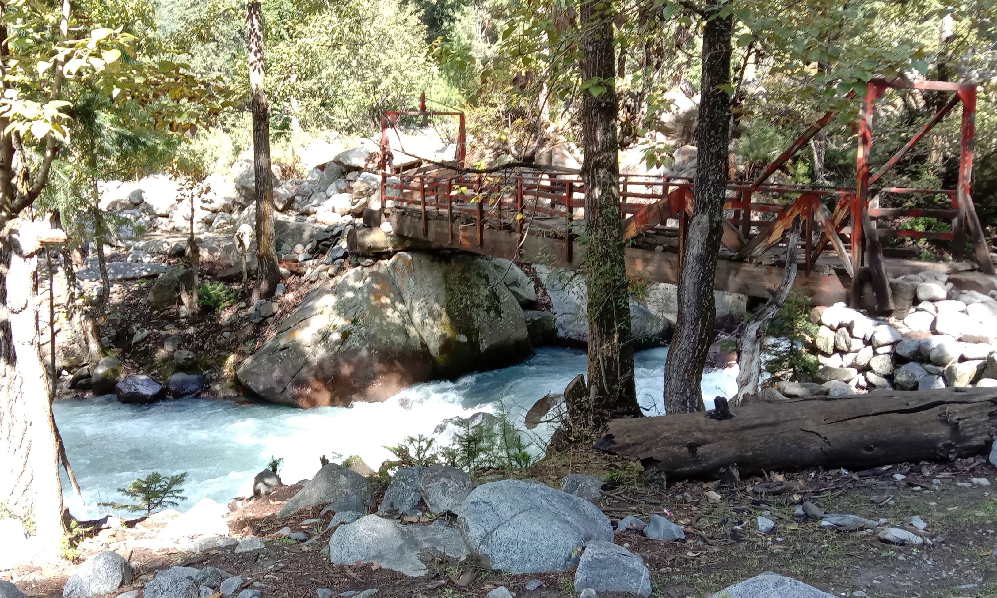 کنڈل جھیل کا پانی اور نالے کو عبور کرنے کے لیے بنایا گیا لکڑی کا پُل—تصویر: عظمت اکبر