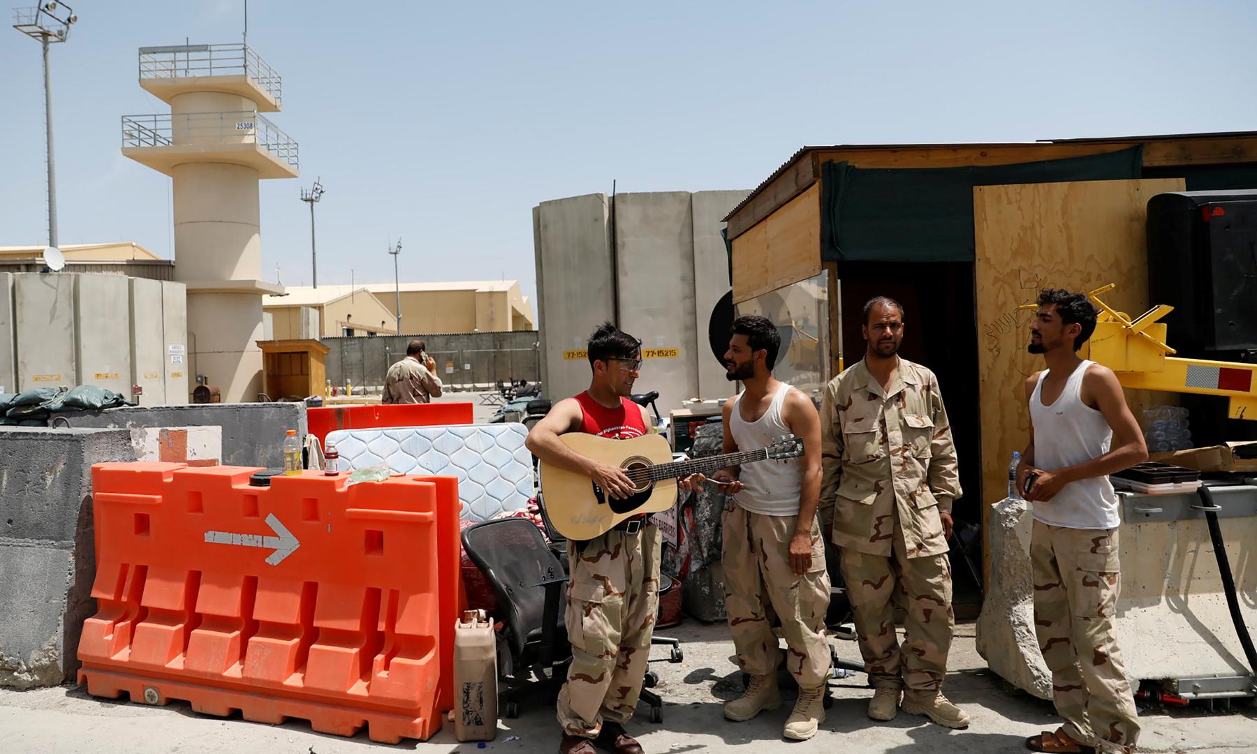 افغان فورسز کے اہلکار امریکی فوج کی جانب سے چھوڑے گئے گٹار استعمال کررہے ہیں—رائٹرز