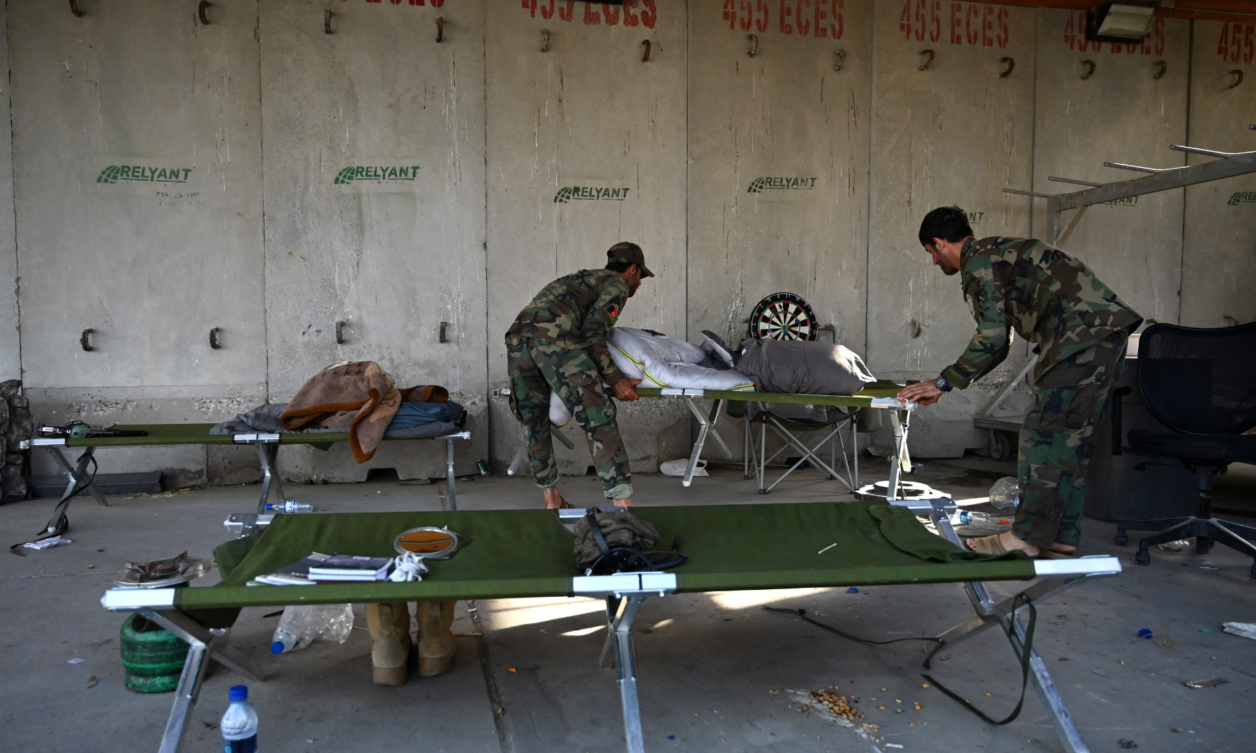 Afghan National Army (ANA) soldiers carry stretchers inside the Bagram US air base after all US and Nato troops left, some 70 kilometres north of Kabul on Monday. — AFP