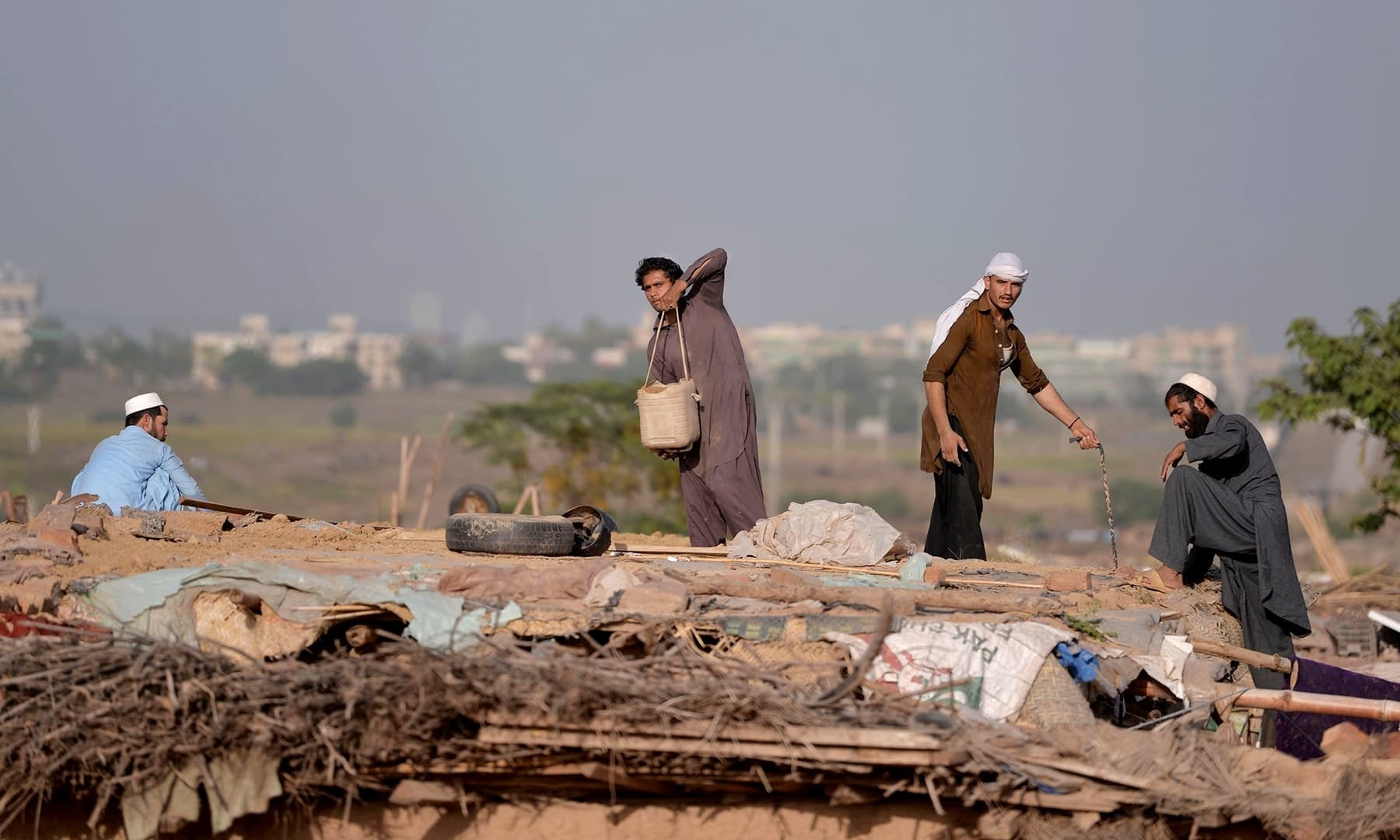 In this file photo, Afghan refugees make a roof for a mud house at a refugee camp. — AFP/File