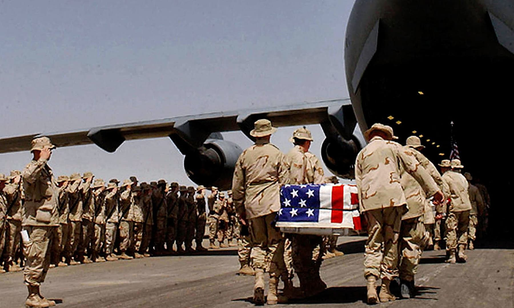 In this file photo taken on March 30, 2003, US soldiers carry the coffins of their colleagues draped in national flags to a C-17 aircraft during a memorial ceremony held at Kandahar army base. — AFP