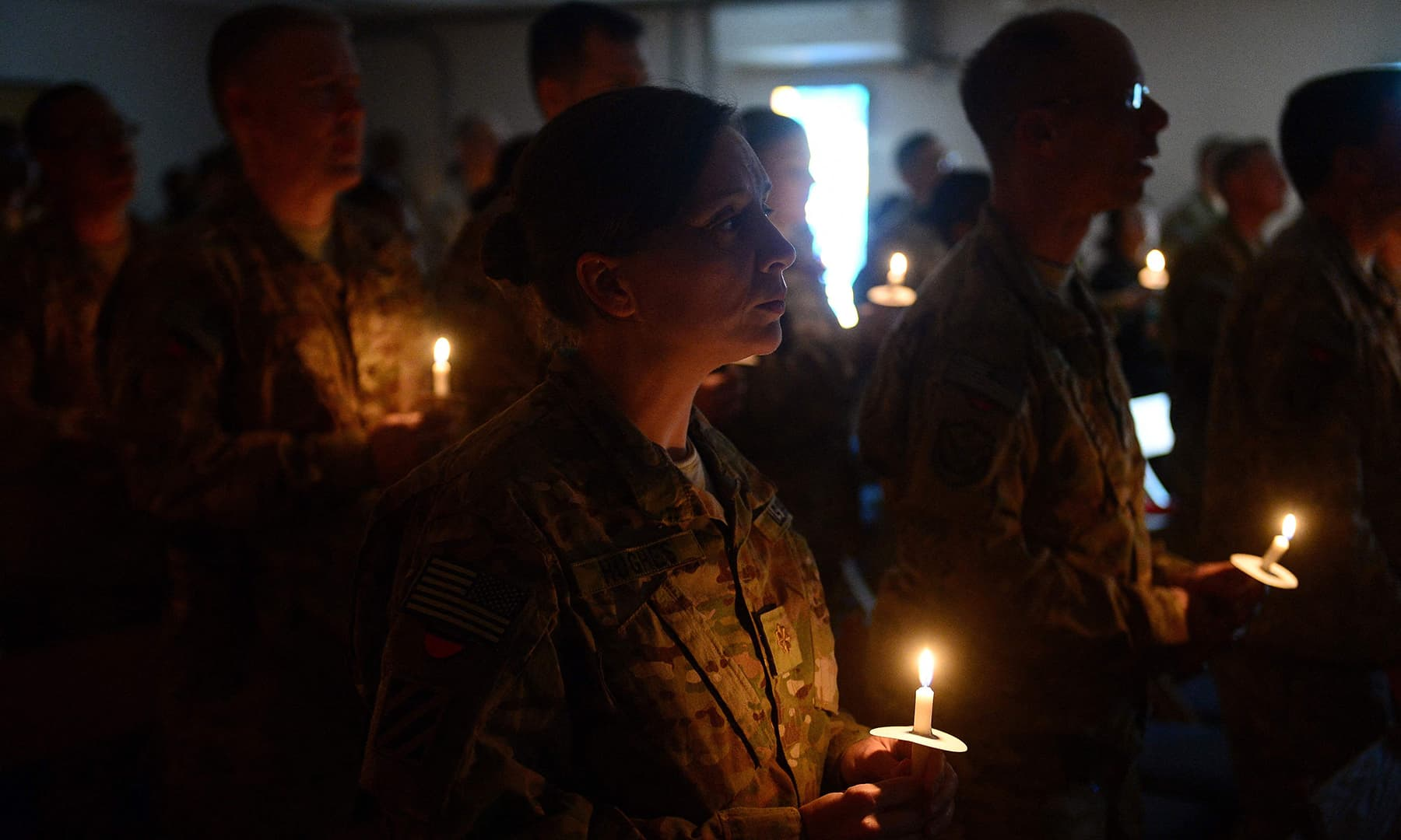 In this file photo taken on December 24, 2013, US soldiers hold candles as they attend a religious ceremony on Christmas Eve at a US military base in Kabul. — AFP