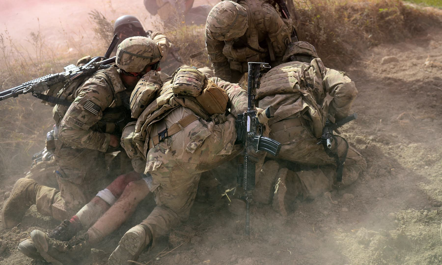 In this file photo taken on October 13, 2012, US Army soldiers attached to 2nd platoon, C troop, 1st Squadron (Airborne), 91st US Cavalry Regiment, 173rd Airborne Brigade Combat Team operating under Nato-sponsored International Security Assistance Force (ISAF) protect a wounded comrade from dust and smoke flares after an Improvised Explosive Device (IED) blast during a patrol near Baraki Barak base in Logar province. — AFP