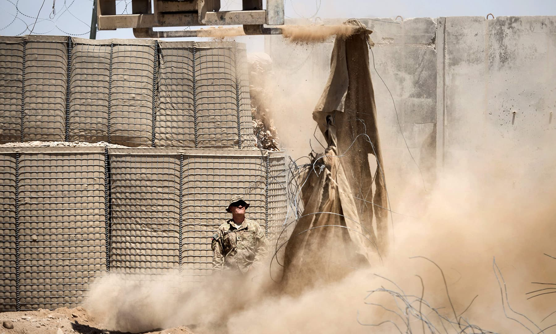 In this file photo taken on June 2, 2014, a US soldier watches as a lift is used to demolish Hesco barriers ahead of the withdrawl from Forward Operating Base Pasab in Kandahar province. — AFP