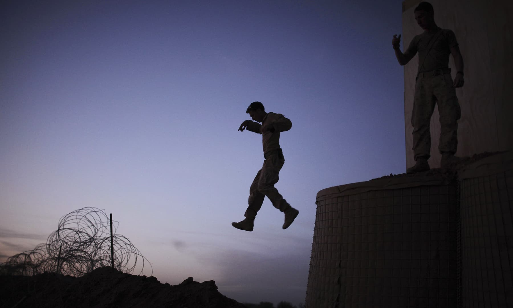 In this file photo taken on March 16, 2010, a US Marine of 3rd Battalion, 6th Marines jumps down to fetch a hammer as they build an observation point on the perimeter of their combat outpost recently set up in Marjah, Helmand province, southern Afghanistan. — AFP