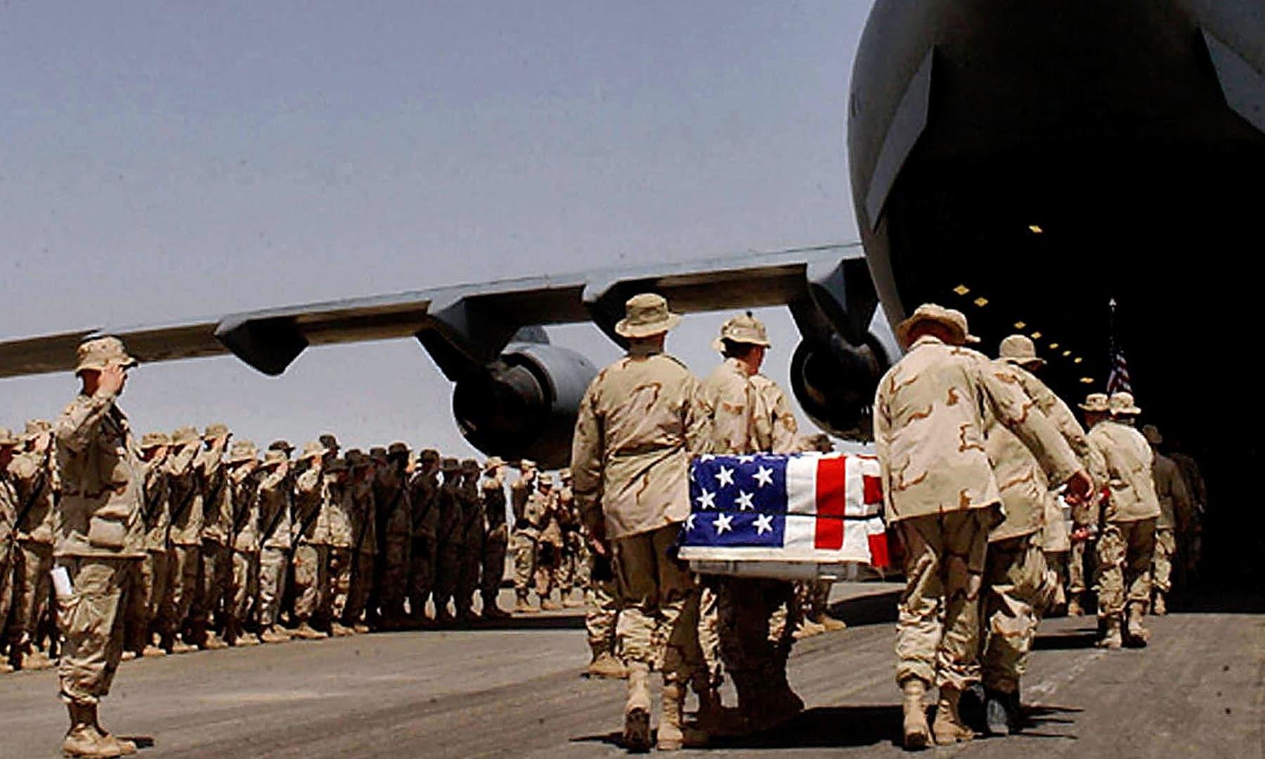 امریکی فوجی 30 مارچ 2003 کو جنگ کے دوران مارے گئے اپنے ساتھی کی لاش امریکا روانہ کر رہے ہیں—فائل/فوٹو: اے ایف پی