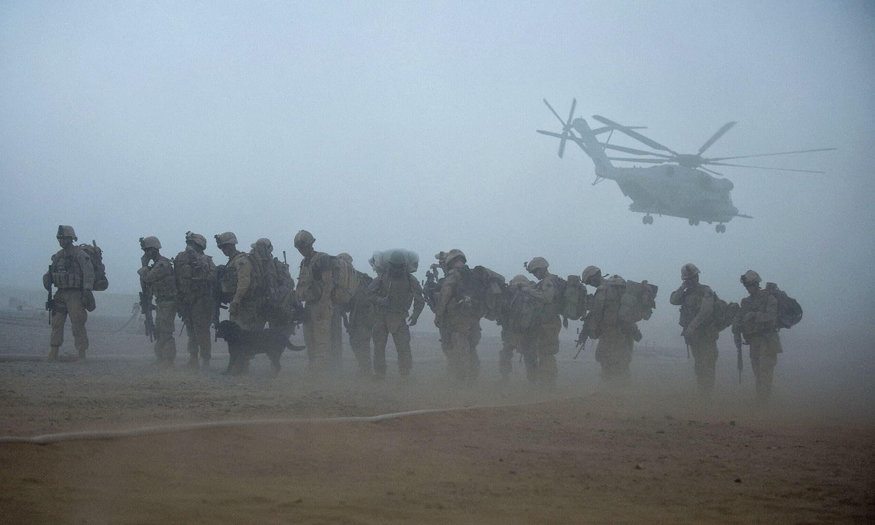 امریکی آٹھویں میرین رجمنٹ کے جوان 2 جولائی 2009 کو ہلمند میں کارروائی کے لیے ہیلی کاپٹر کی جانب بڑے رہے ہیں—فائل/فوٹو: اے ایف پی