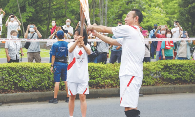ASAKA: The Olympic flame is passed from torch to torch as spectators look on during the Tokyo 2020 Olympic torch relay on the opening day of the relay in the Saitama prefecture on Tuesday.—Reuters