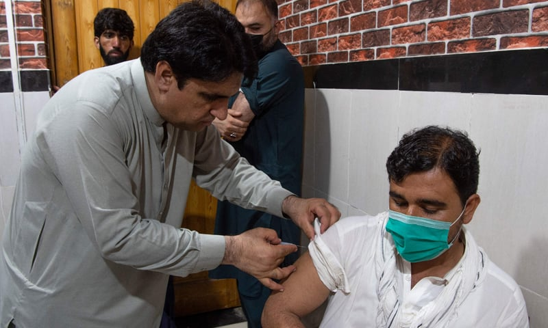 An overseas Pakistani worker who wants to fly to the Middle East receives a dose of the Moderna vaccine at a vaccination center in Peshawar. — AFP