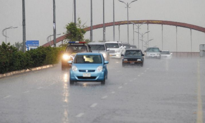Vehicles travel on 7th Avenue as rain lashes Islamabad. — Photo by Mohammad Asim/File