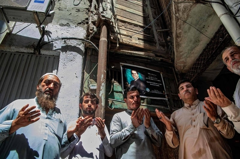 People pray for late Bollywood actor Dilip Kumar, who died today in Mumbai at the age of 98, outside his ancestral home in Peshawar on July 7. — AFP