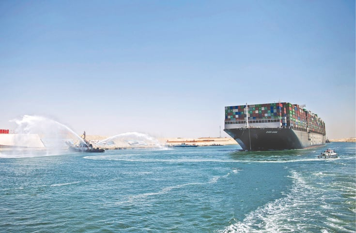 The MV Ever Given container ship sails past a tugboat spraying a jet of water along Egypt's Suez Canal, near Ismailia.—AFP