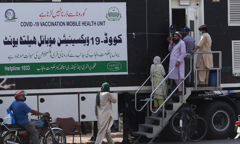 People wait for their turn to get a dose of a vaccine against the Covid-19 coronavirus outside a mobile vaccination health unit in Lahore on July 7. — AFP