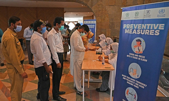 People register to get a dose of the Covid-19 vaccine at a mass vaccination center in Islamabad. — AFP/File