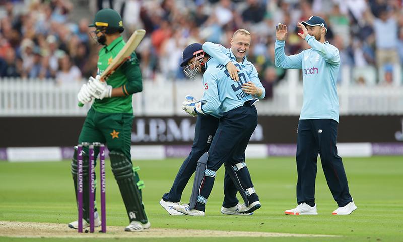 دوسرے ون ڈے میچ میں شاداب خان کی وکٹ لینے کے بعد انگلش کھلاڑی میٹ پارکنسن کو مبارکباد دے رہے ہیں— فوٹو: اے ایف پی