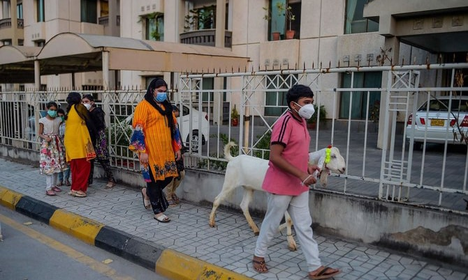 Children wearing facemasks walk with a goat ahead of Eidul Azha in Rawalpindi. — AFP/File