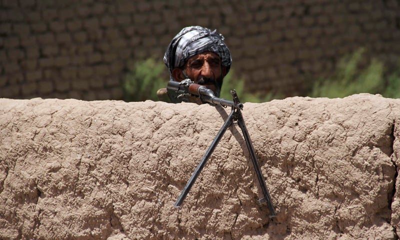 A former Mujahideen watch at a check post as he holds a weapon to support Afghan forces in their fight against Taliban on the outskirts of Herat province, Afghanistan. — Reuters